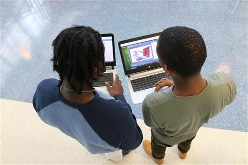 Two students on laptops  in a hallway